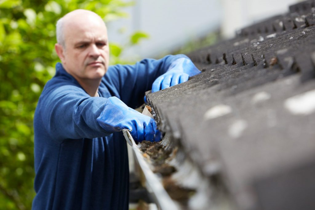Man with gloves cleaning out gutter